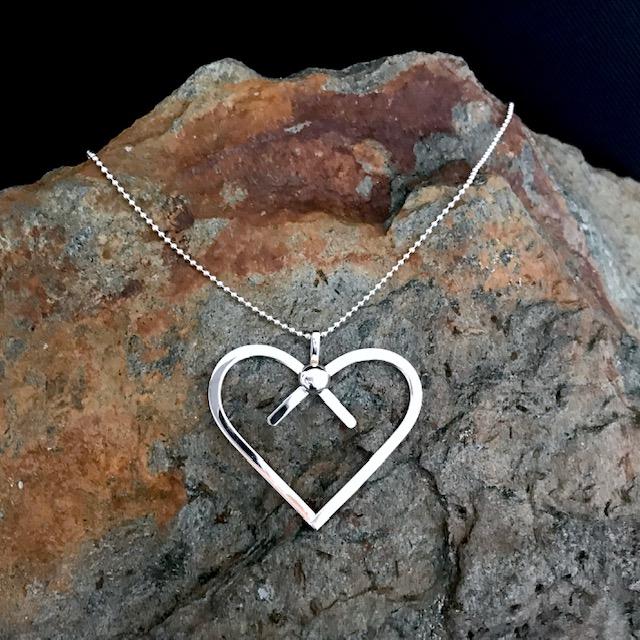 MIINA Rosetthjärta har en stilren och lekfull design med en rosett och hjärta i ett. Blank polerad kula på hjärta  Mått ca 48x40 mm  Levereras med 60 cm kulkedja i silver.
